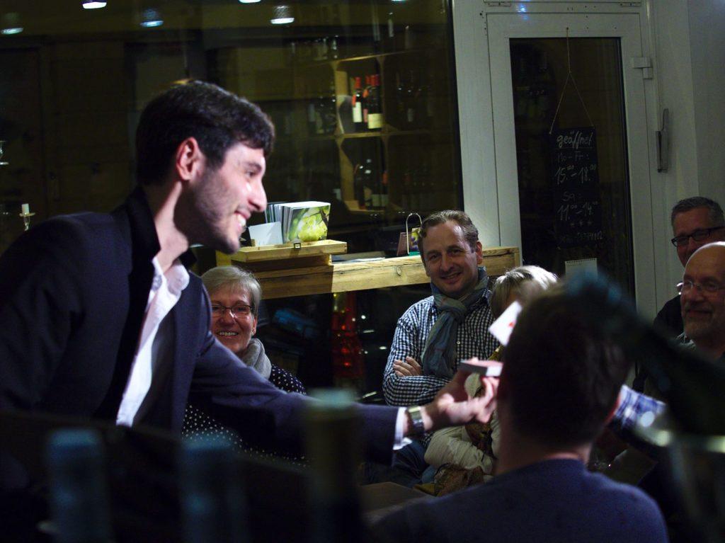 Alfonso Rituerto überreicht das Kartenspiel den ZuschauerInnen, sodass sie selber zaubern.